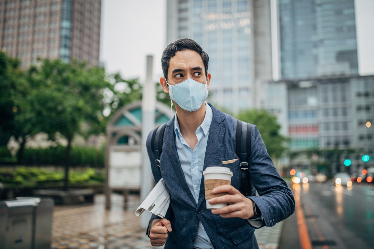 man in suit holding newspaper and coffee and wearing a face mask in city