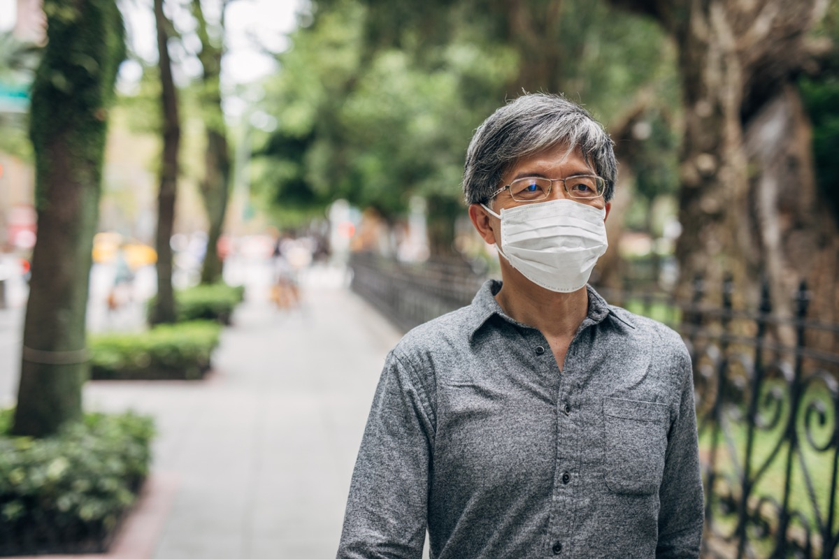 older asian man walking with face mask outside