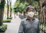 older man walking with face mask outside