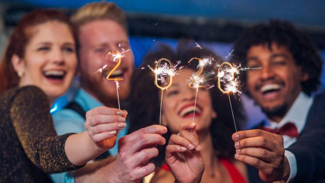 happy young friends holding up 2020 sparklers at new year's party