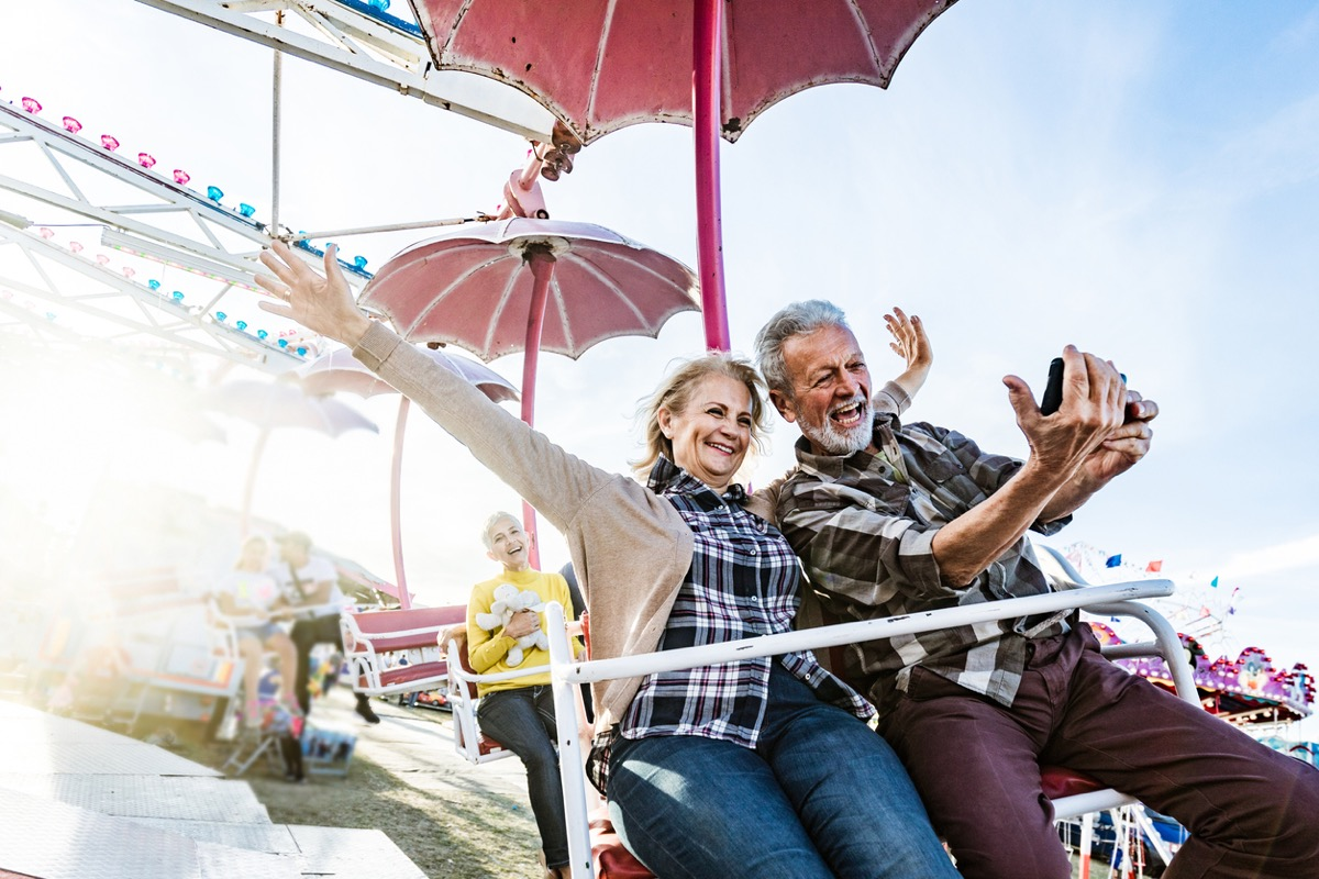 older white couple taking a selfie on a carnival ride