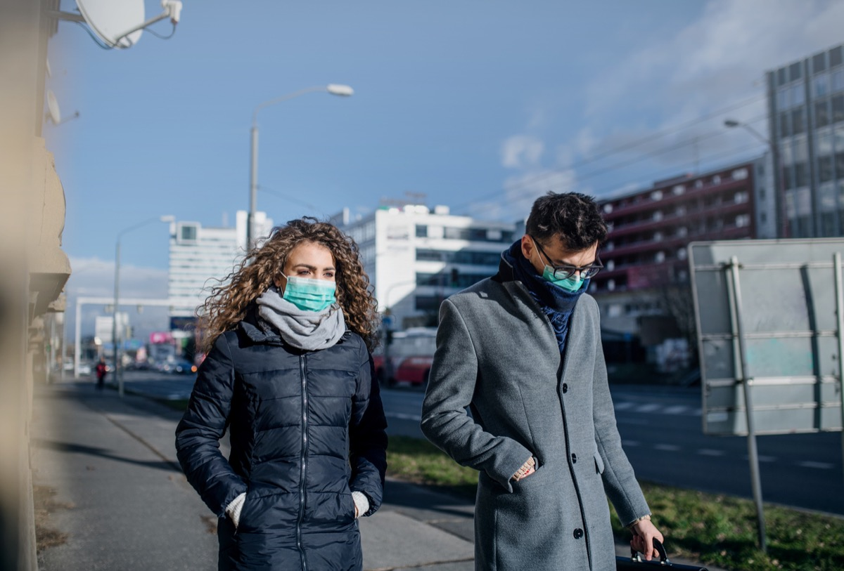 white woman and man walking in face masks in a city
