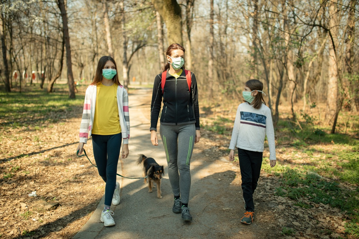 mother and two daughters in face masks walking their dog in a park