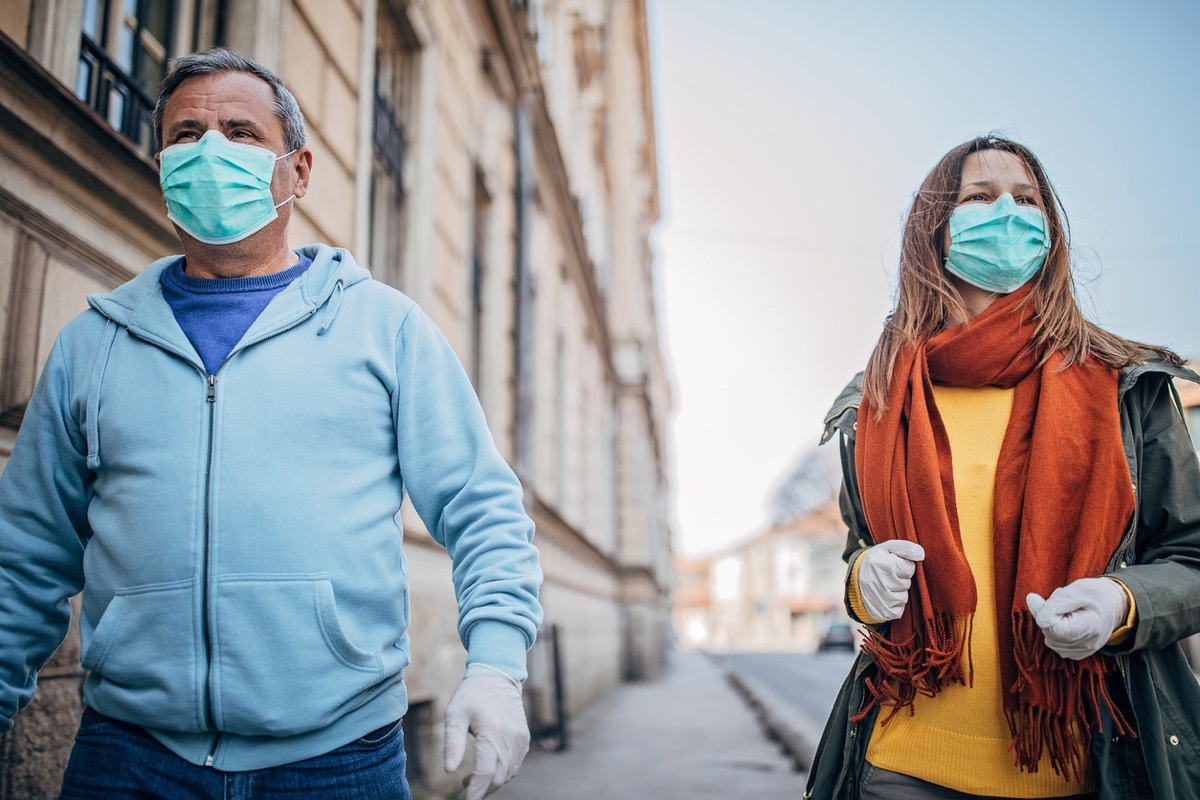 older white man and woman with masks walking outside