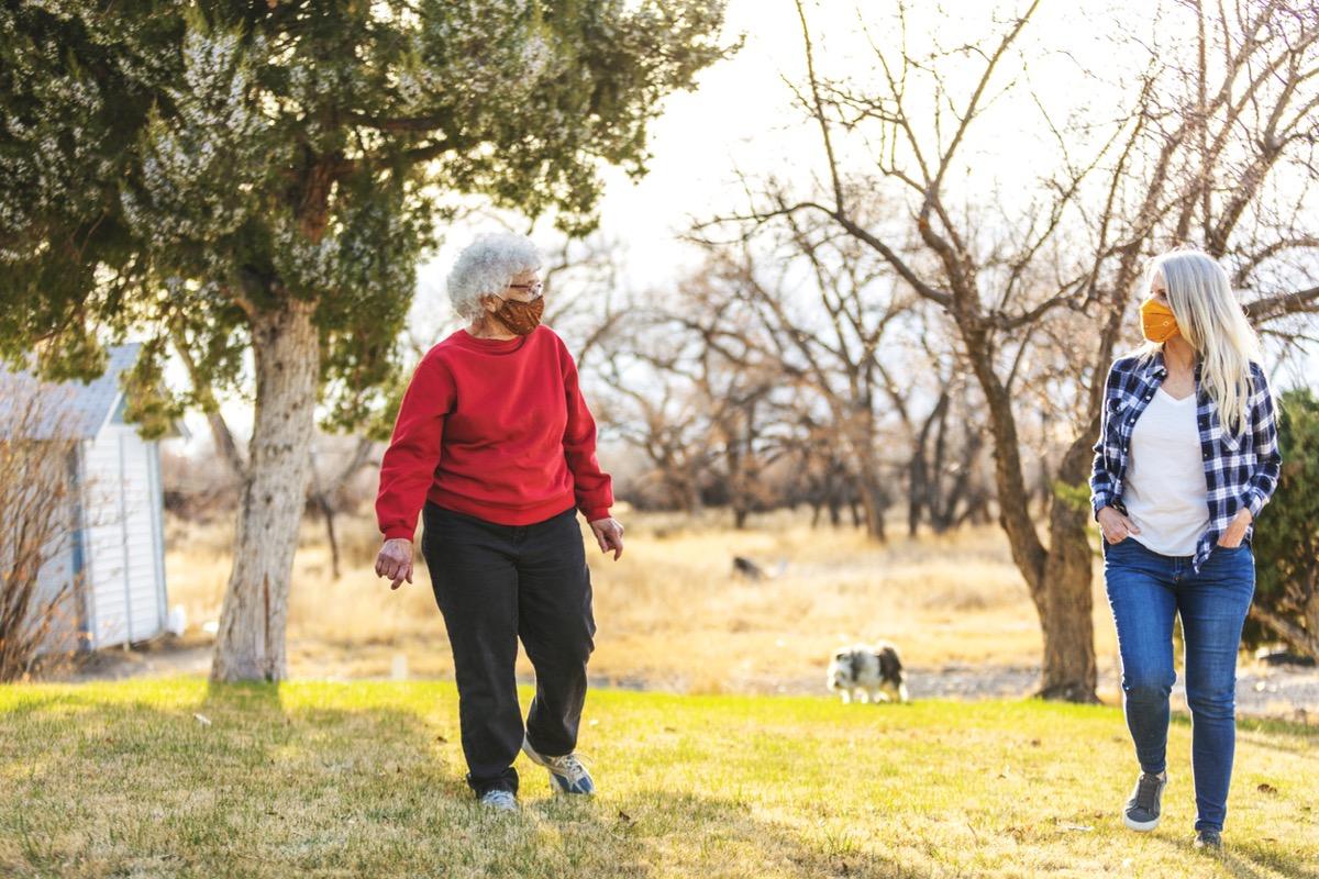 older white women walking with face masks six feet apart