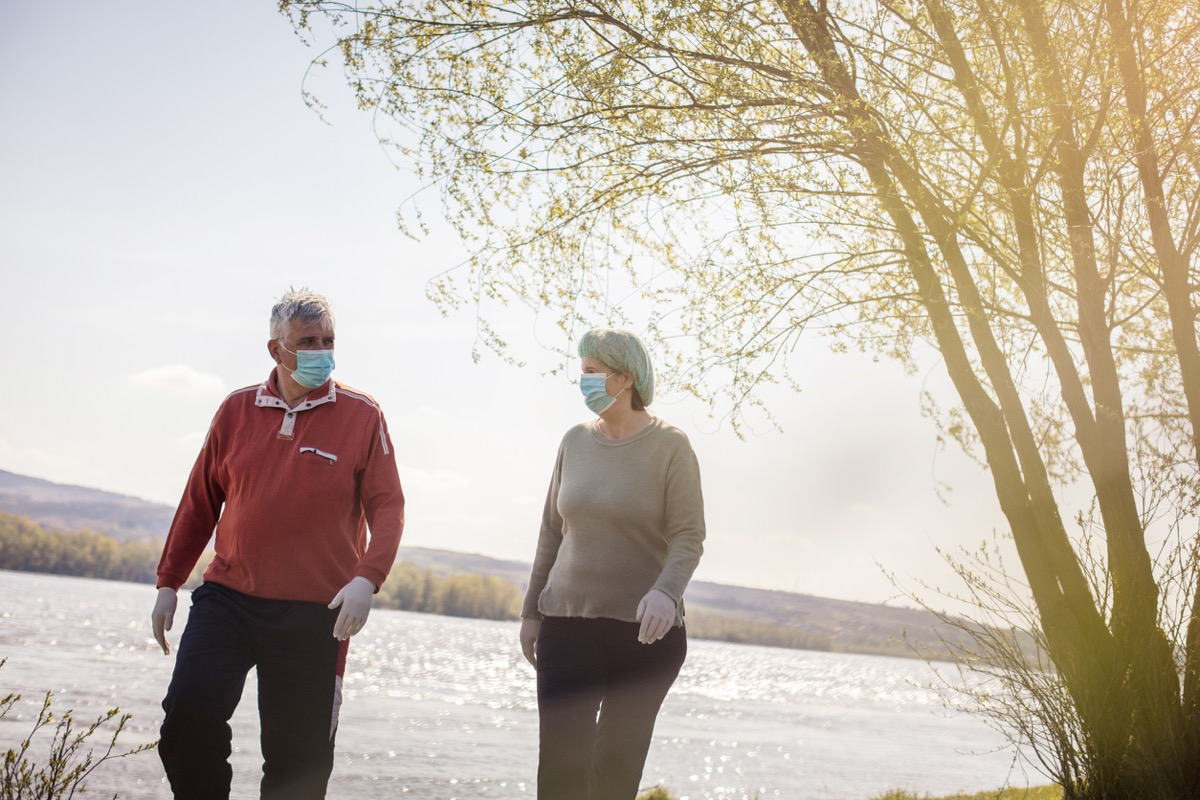 older white man and white woman walking by the water with face masks