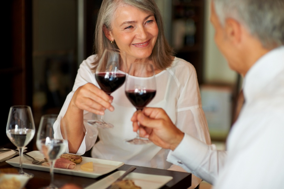 older white couple toasting red wine at dinner