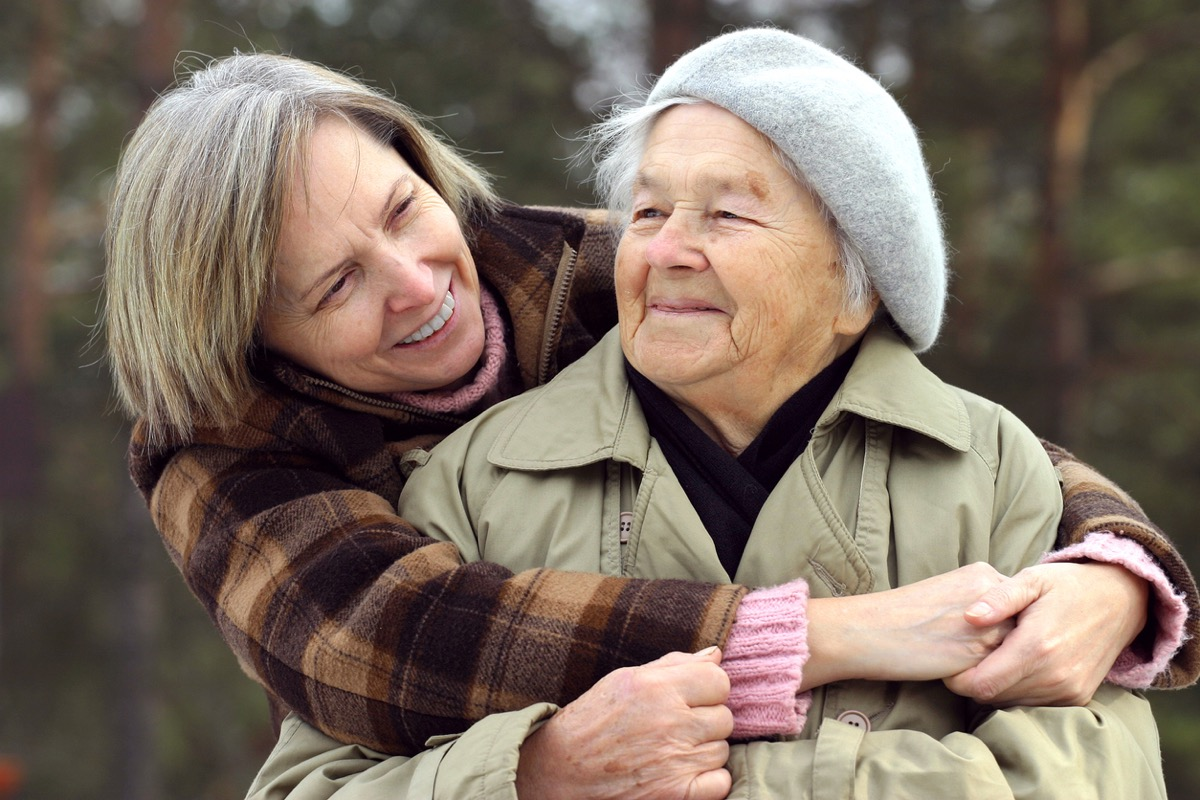 middled aged white woman hugging her mother from behind