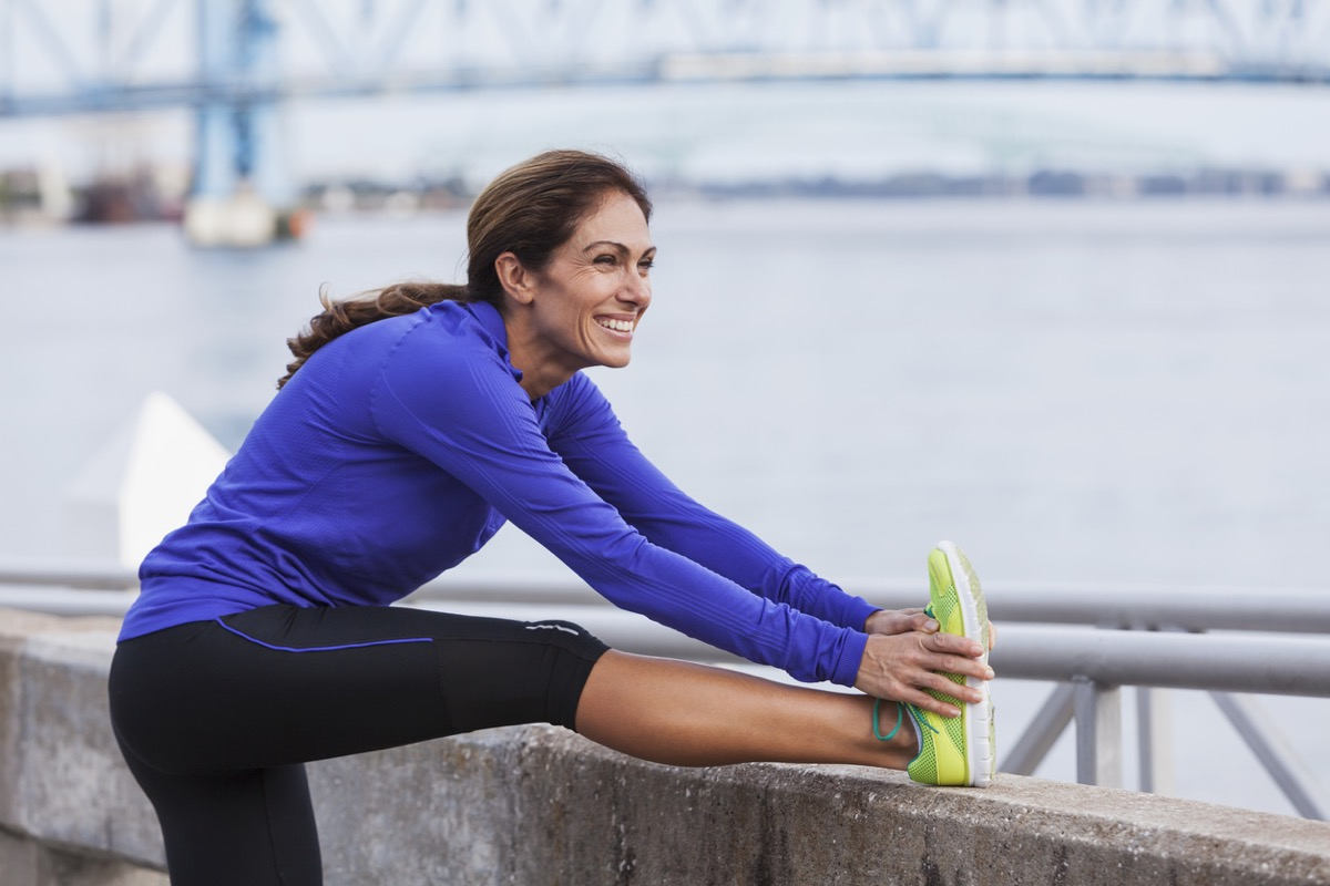 white woman runner stretching by the water