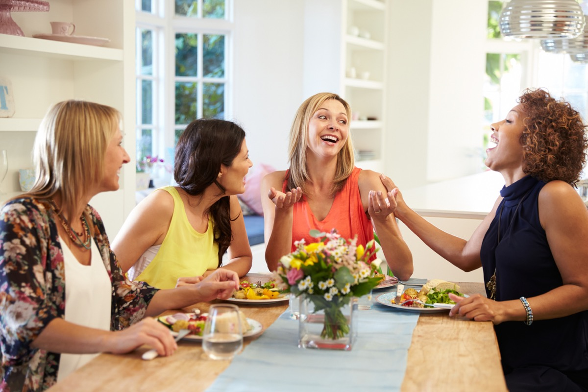 four women laughing and eating at a dinner party