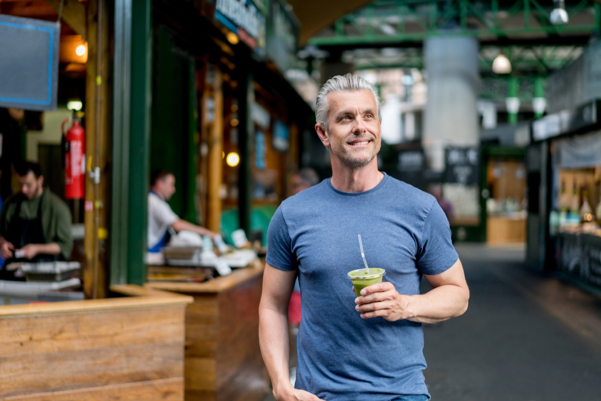 white man with gray hair drinking a smoothie outside