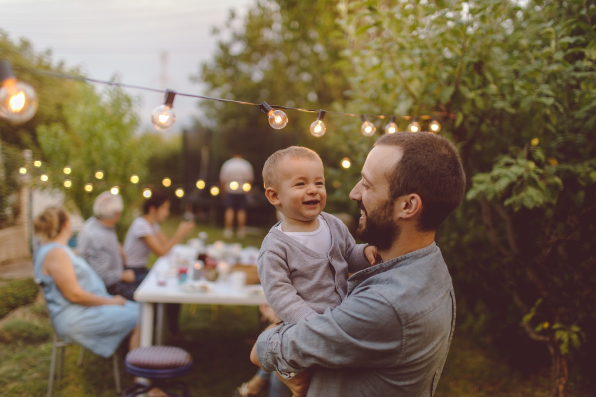 white man holding baby and smiling at outdoor party
