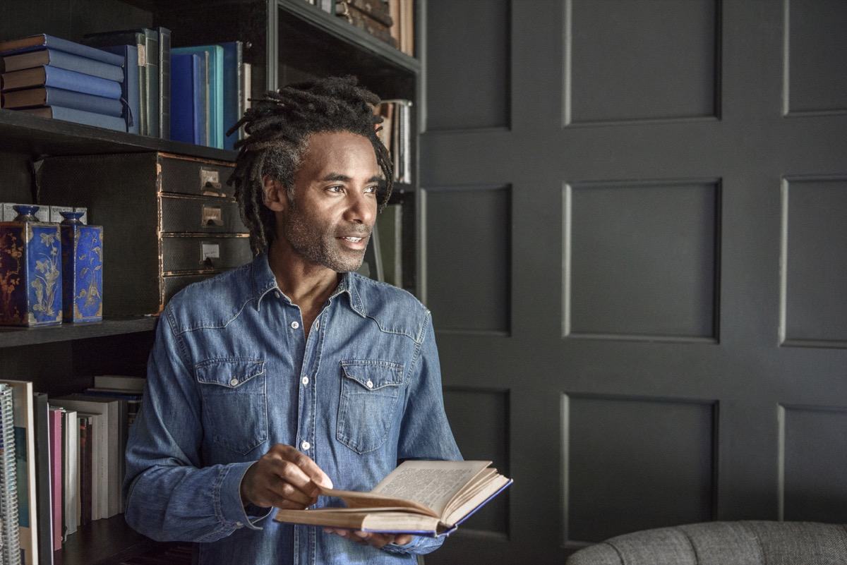 middle aged black man holding open a book next to his bookshelf