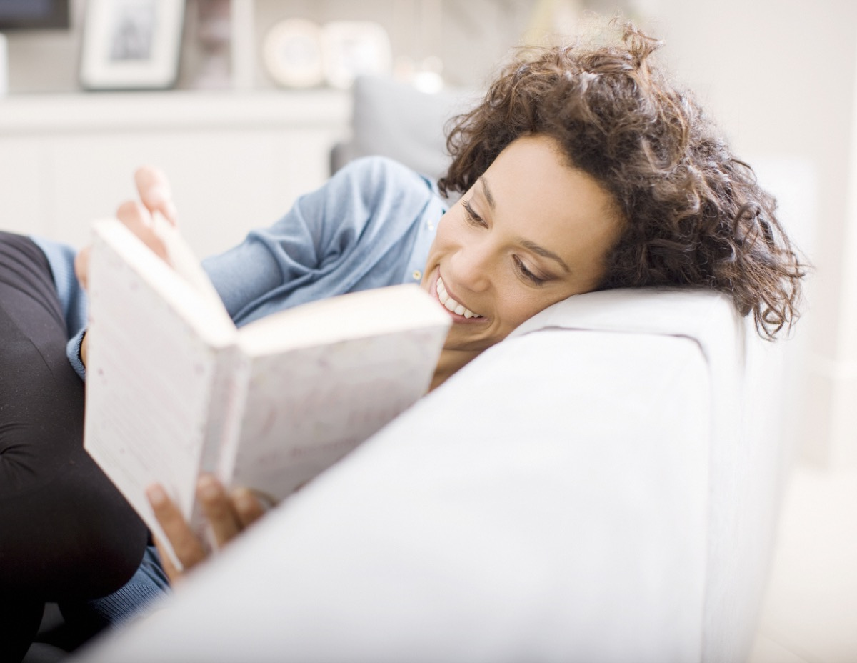 latina woman reading a book on the couch