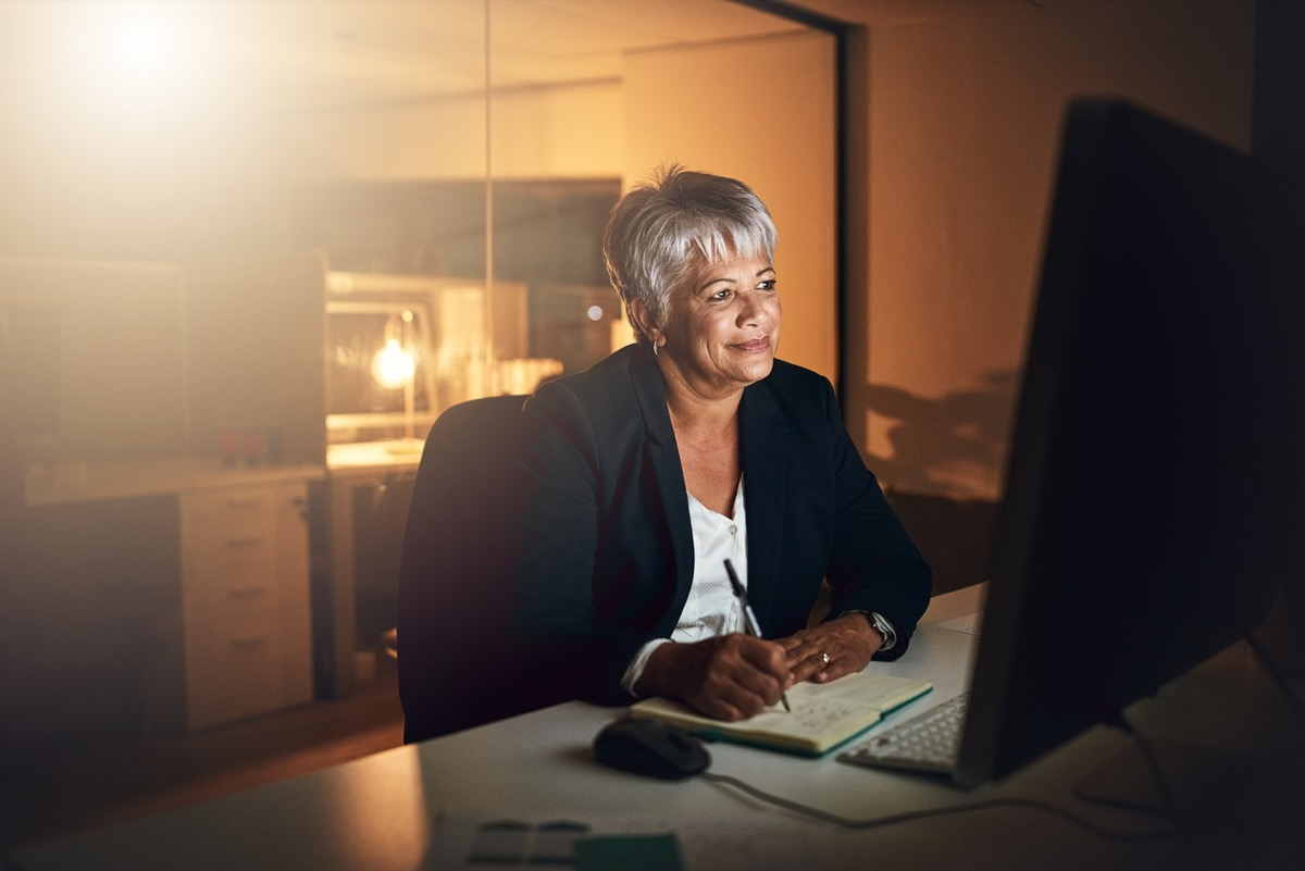 older black woman on her office computer at night