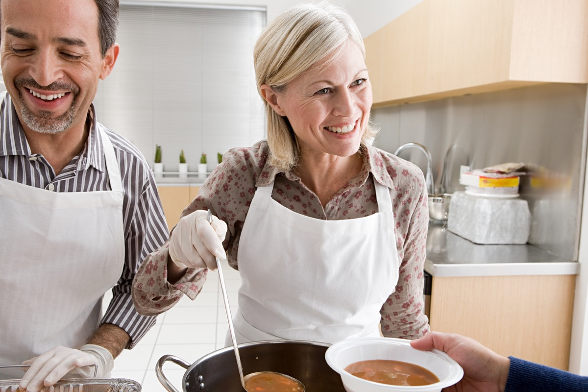 middle aged white couple volunteering at a soup kitchen