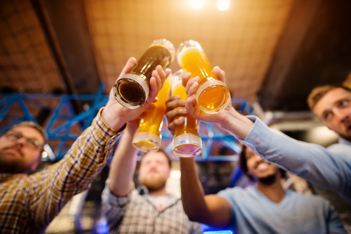 close up from below of four beers being toasted by young men