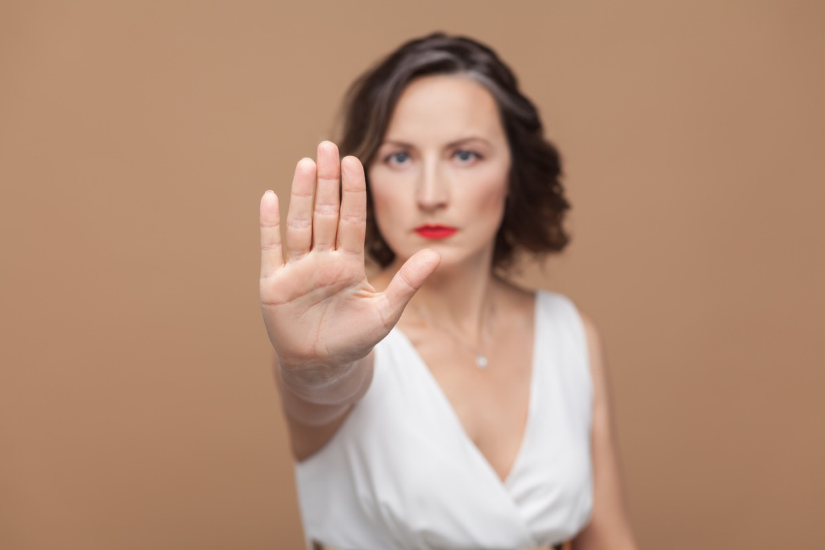 white woman putting up her hand to say stop