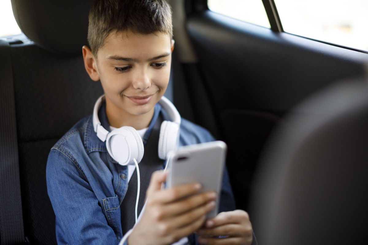 teenage boy using mobile phone in the car