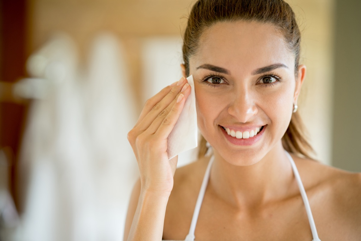 portrait of a beautiful woman cleansing her face with a pad and removing her make up while looking at the camera smiling