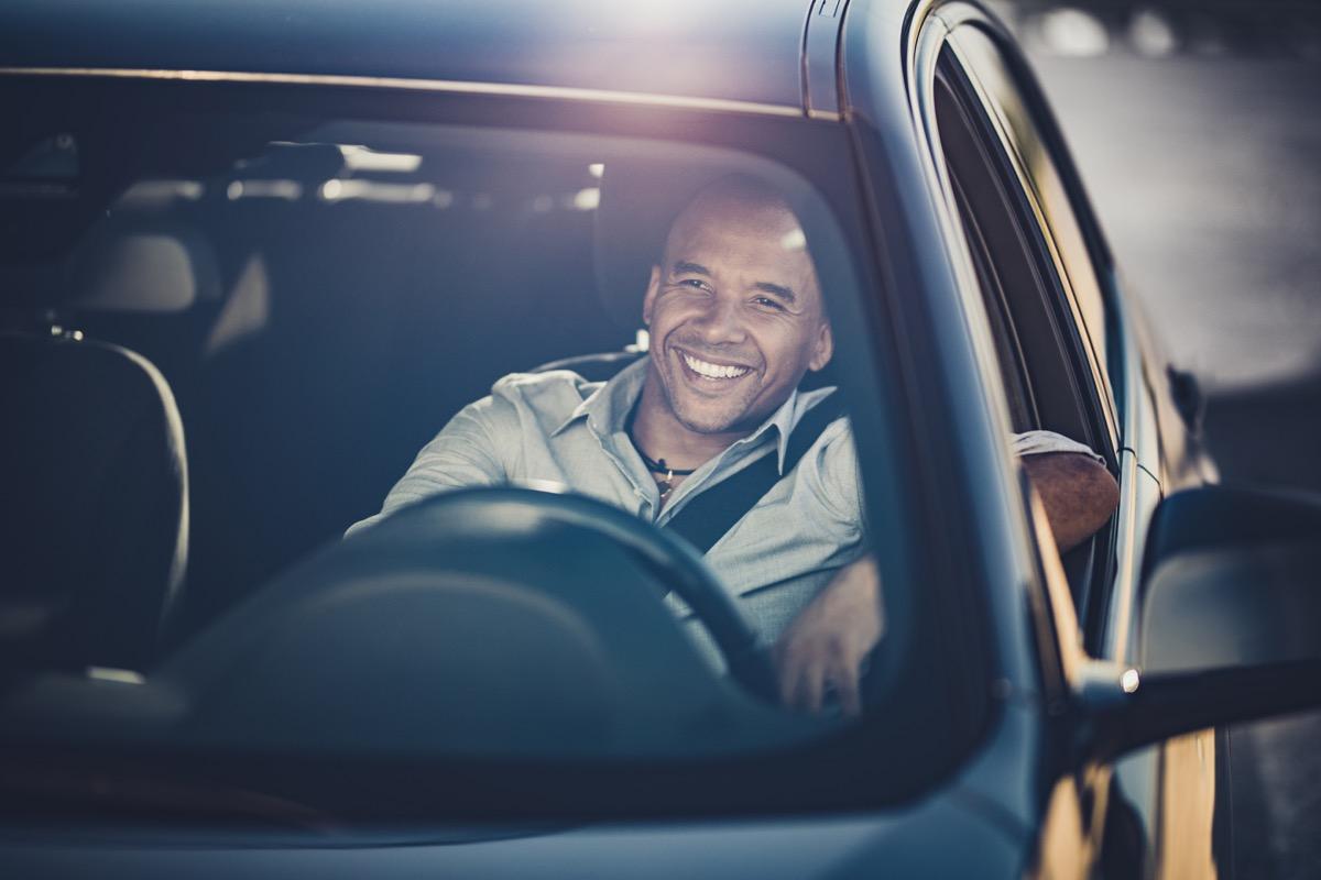Happy black businessman enjoying while driving a car.