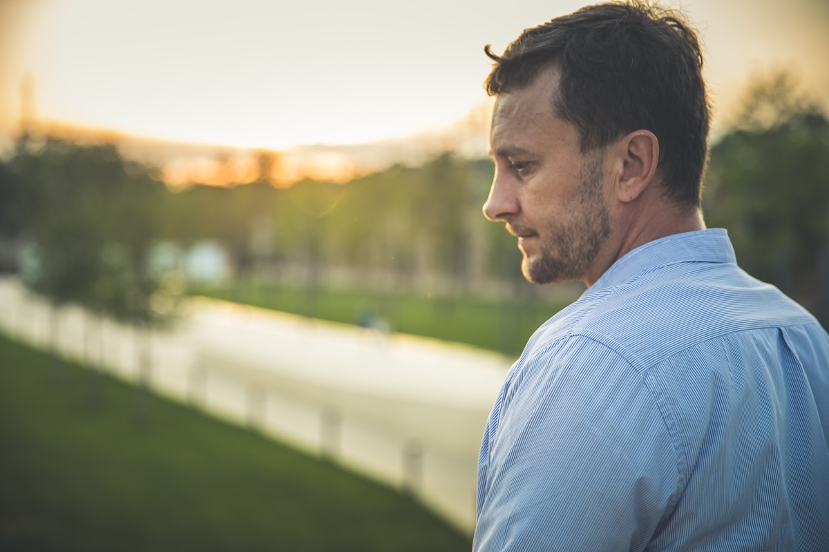 Portrait of handsome middle-aged man in sunmmer morning park. Pensive calm man in casual clothes overgreen nature outdoor.