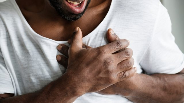 man clutching chest having heart problems