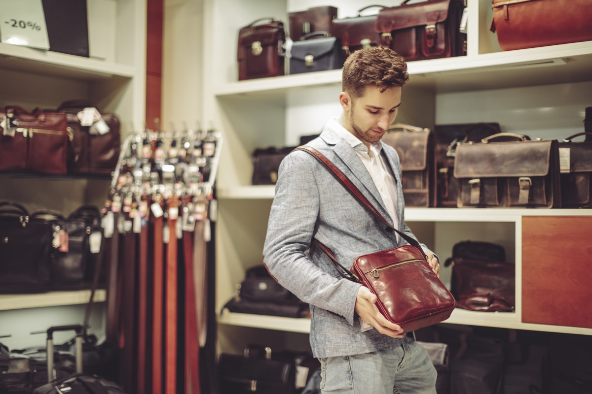 man standing with satchel he cannot afford in a store