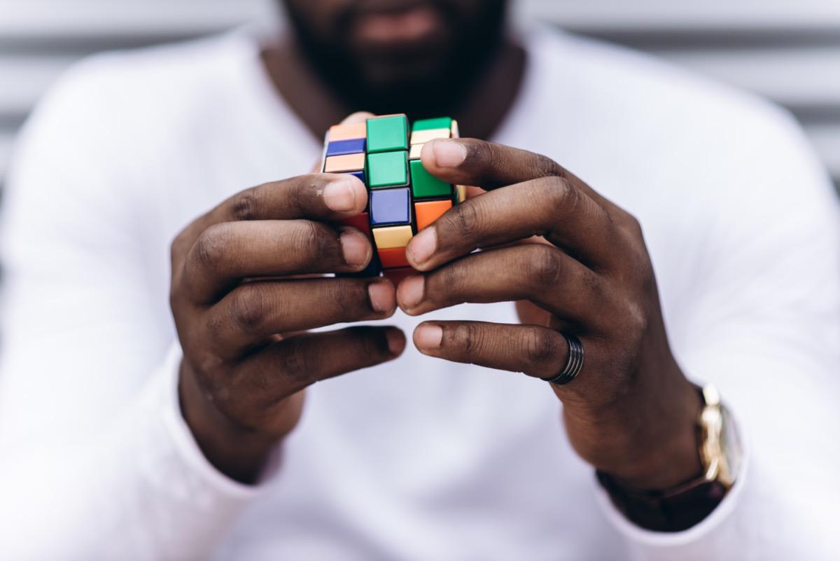 man solving a rubiks cube