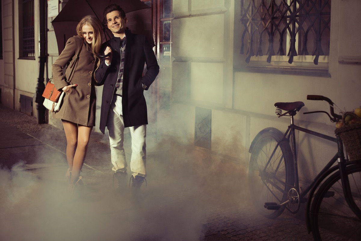 man and woman wearing long coats waking outside after a date
