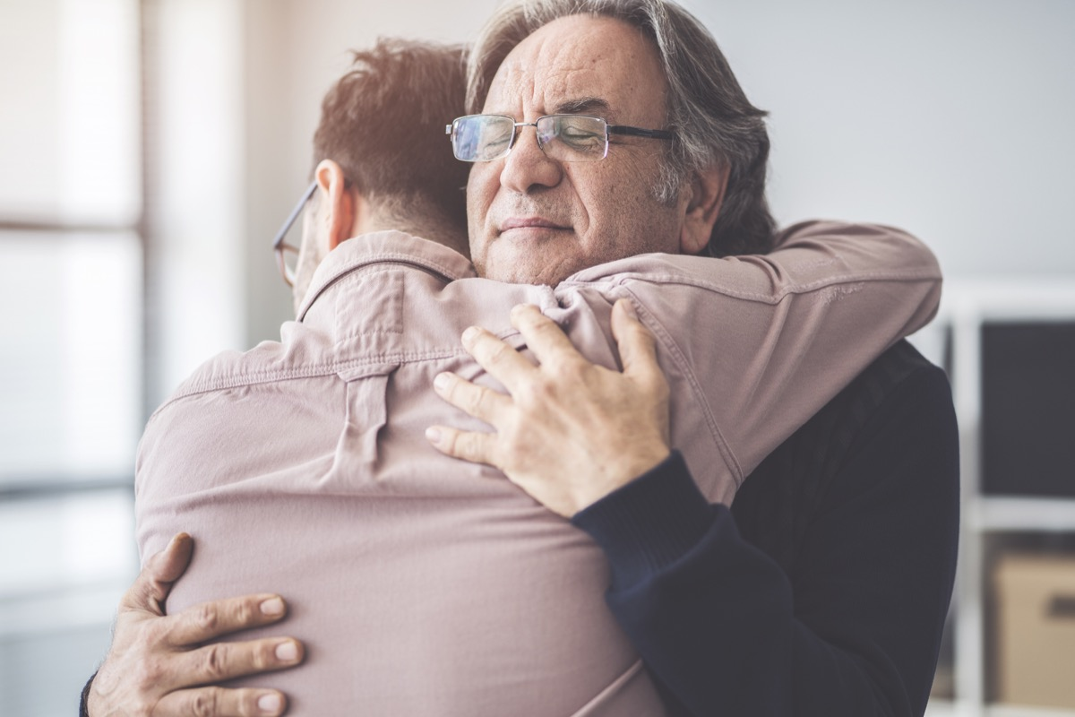 father hugs his adult son