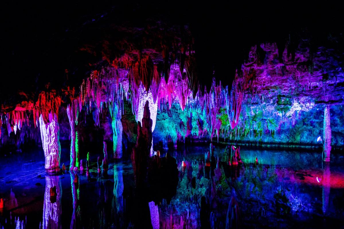 colorful light illuminates the rock formations inside meramec cavern