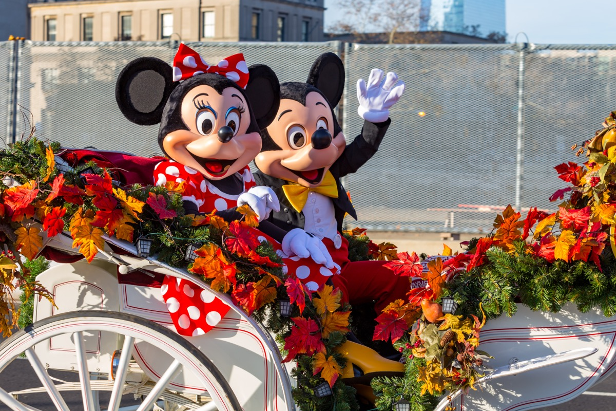 mickey mouse and minnie mouse riding in a thanksgiving parade float together