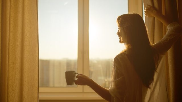 Woman opening curtains in morning with coffee