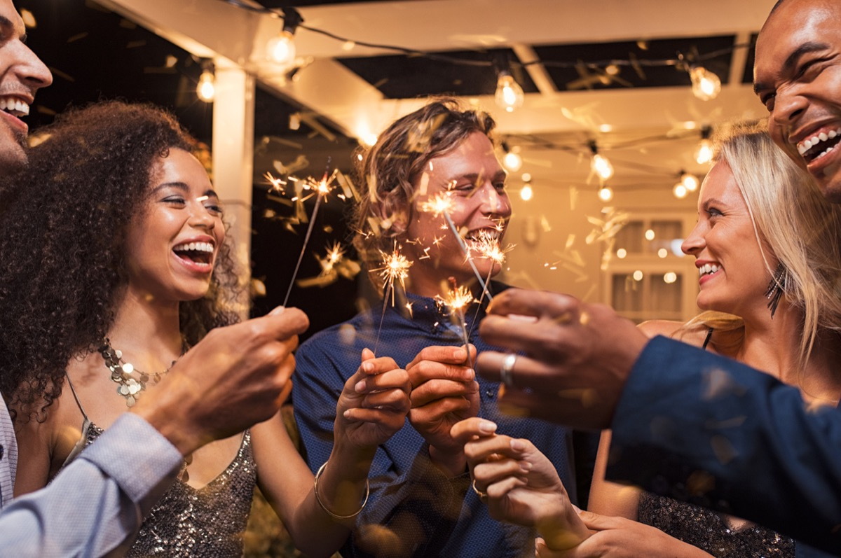 multiracial group of 30-something friends celebrating new year's eve with sparklers