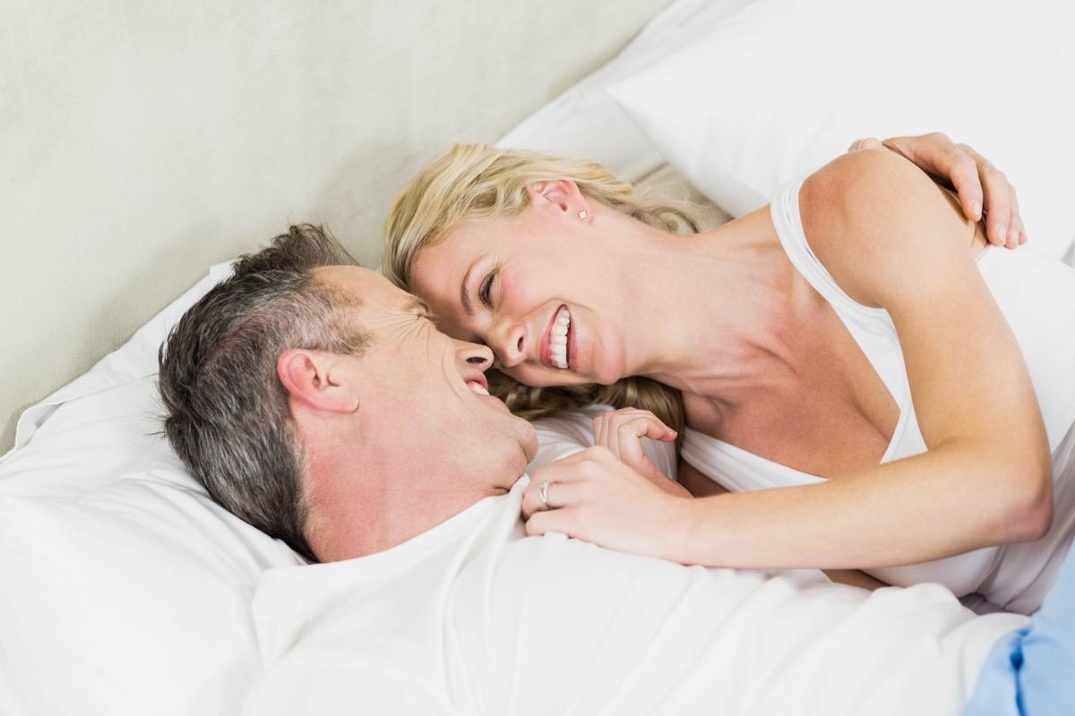 older couple cuddling in bed together