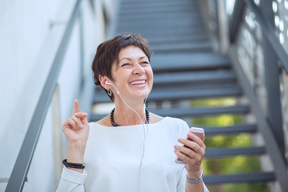 Content mature woman in trendy clothes listening to music with headphones and phone on street smiling away