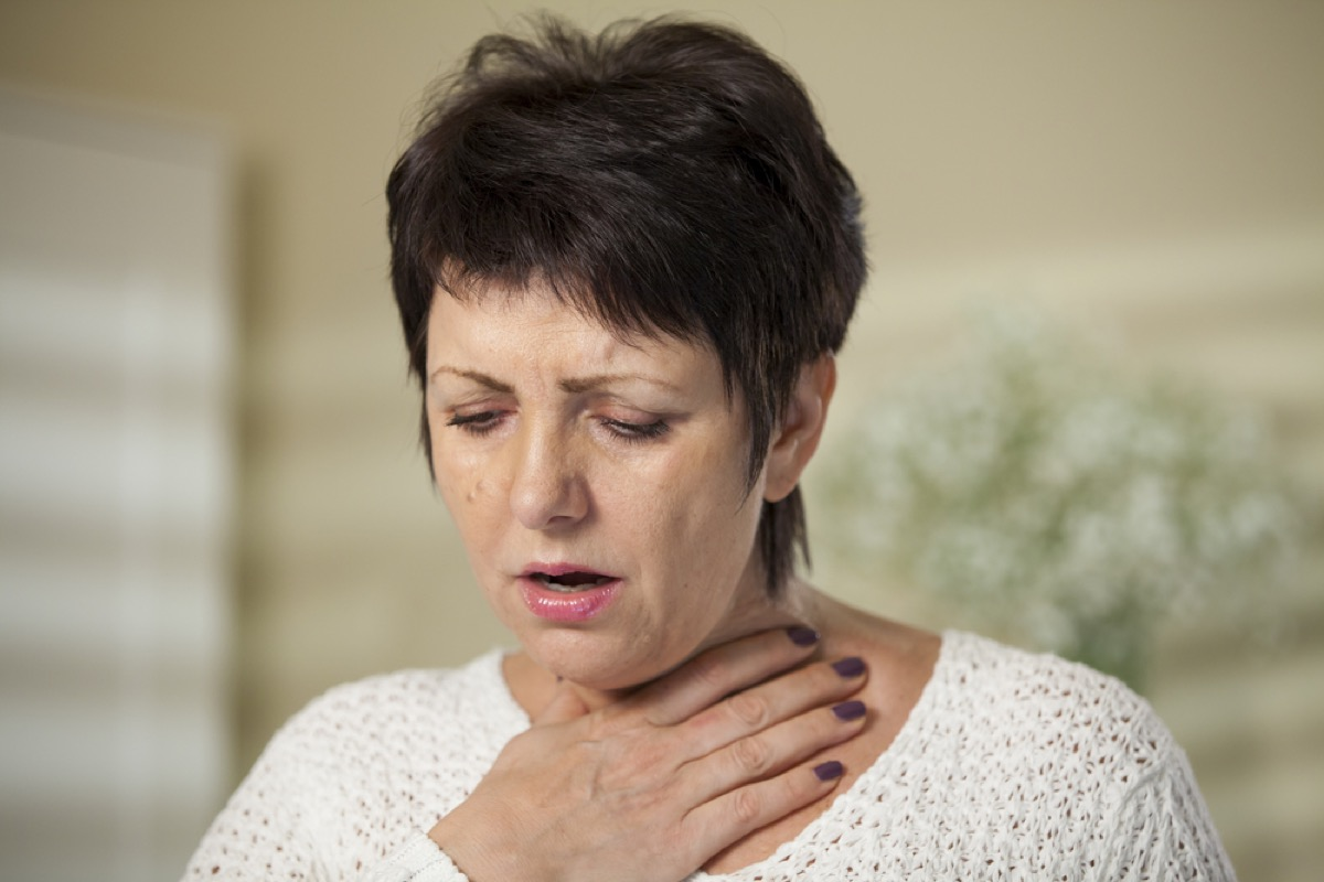 older woman clutching throat, signs your cold is serious