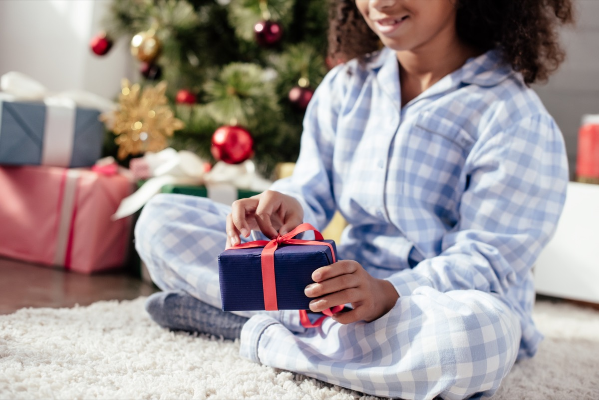 Little girl opening Christmas presents in pajamas