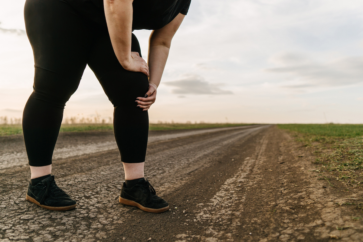 Overweight woman touching pain in leg