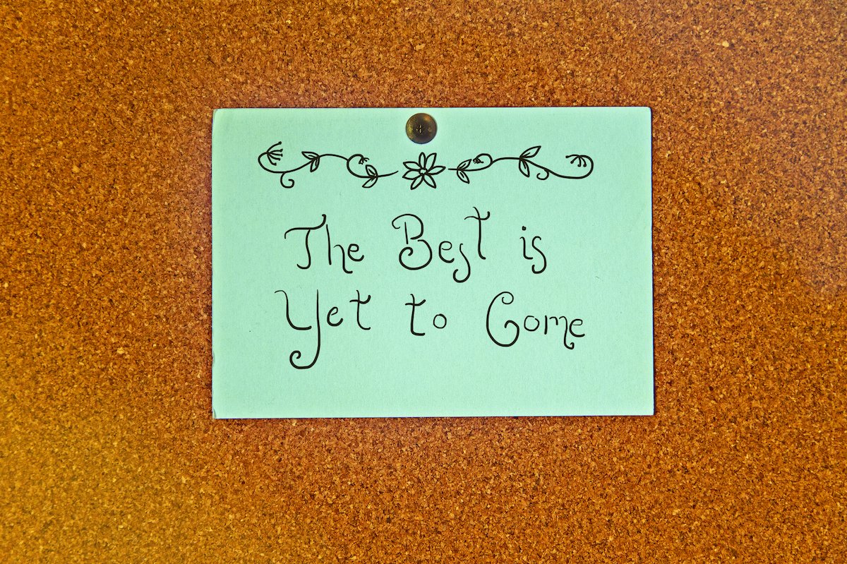 """positive post it note reads """"the best is yet to come"""" on cork board"""