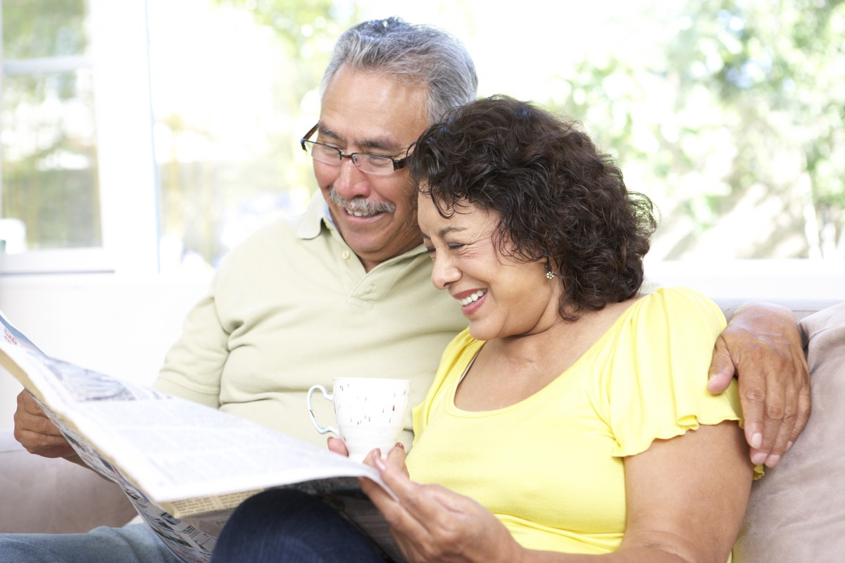 Older couple happily reading newspaper