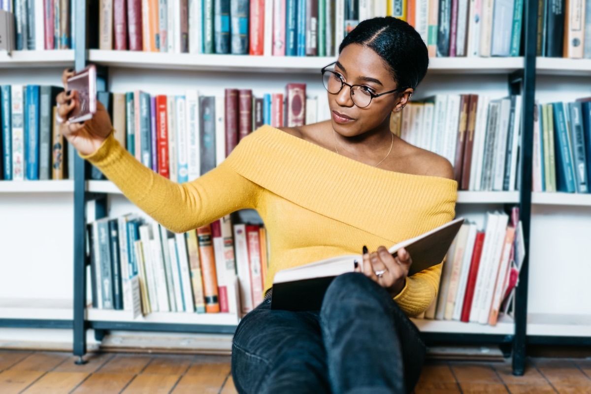 african american young woman student in eyewear making selfie photo on front camera of smartphone for sharing in networks sitting with literature book on floor and preparing for exam in library