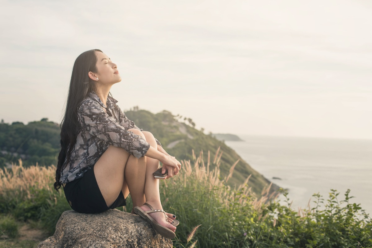 relaxed woman sitting in the grass by the ocean