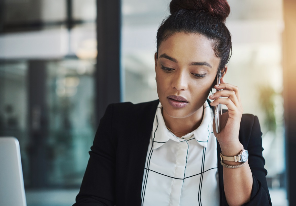 Shot of a young businesswoman using a mobile phone in a modern office