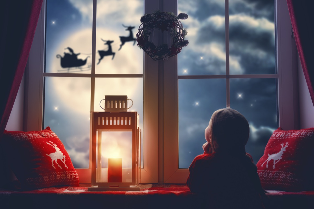 Little girl staring outside her window at Santa's sleigh and reindeer in the sky