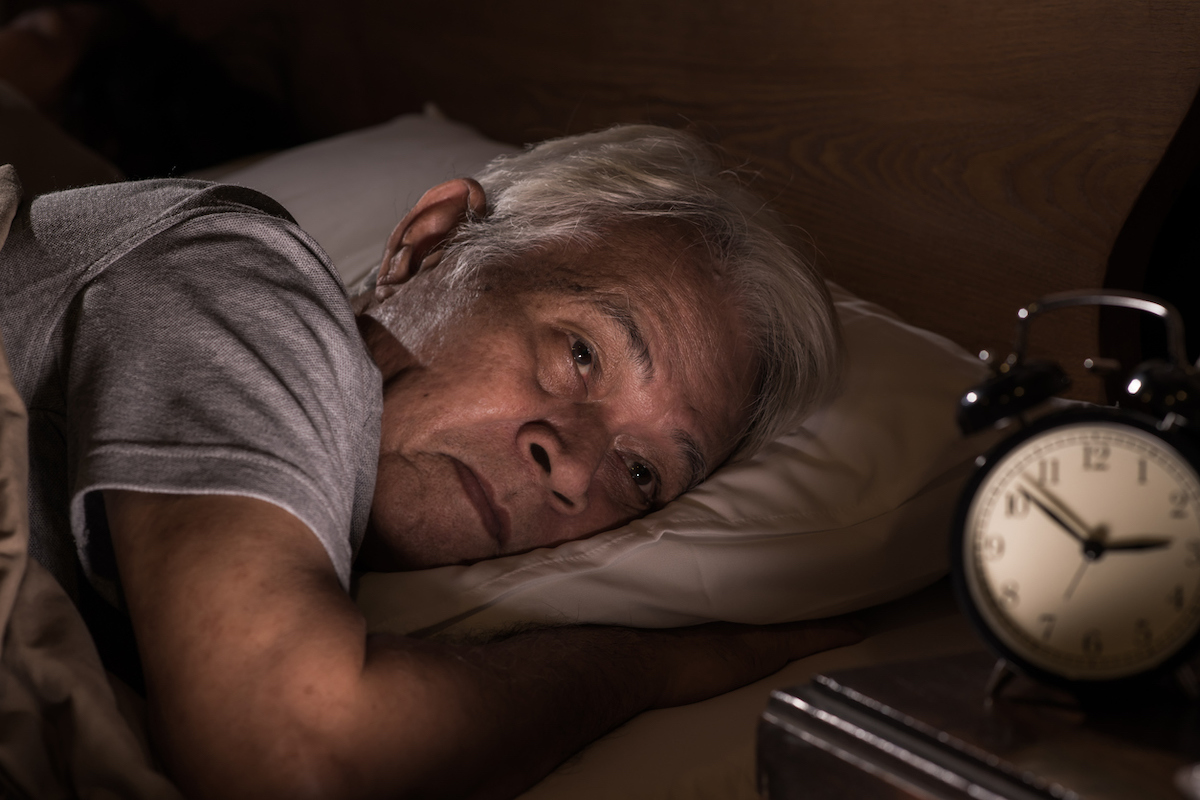 senior asian man lying in bed cannot sleep from insomnia