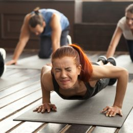 woman doing push ups and looking upset
