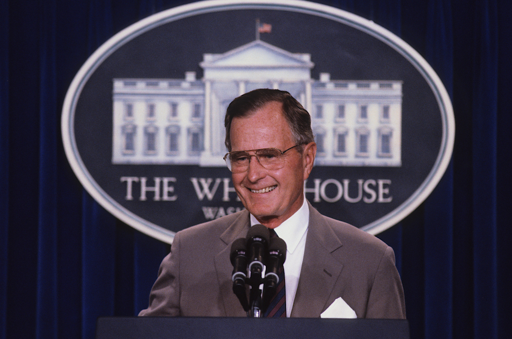 george h.w. bush tands at the podium as he responds to reporters questions during a news conference in the press briefing room at the White House in 1990.