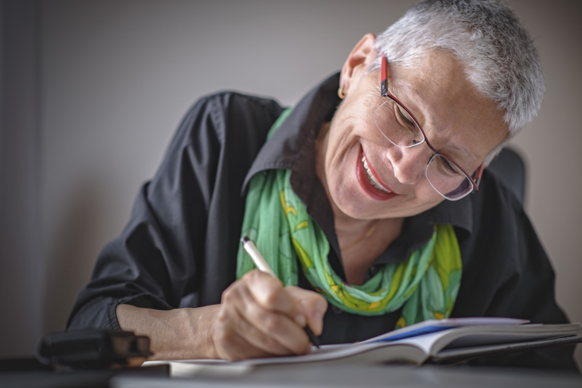older white woman writing in a journal and smiling